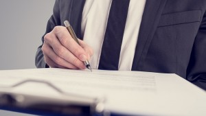 Retro vintage style image of a businessman signing a contract or document on a map.